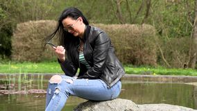 Brunette near the lake with a phone. Sitting on a stone stock video