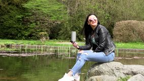 Brunette near the lake with a phone. Sitting on a stone stock footage