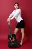 Brunette novo bonito com uma guitarra preta Imagens de Stock Royalty Free