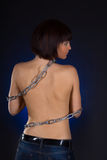 Brunette with nude back in chains over black background Royalty Free Stock Photos