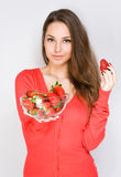 Brunette offering bowl of strawberries. Stock Photos