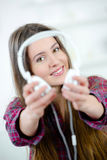 Brunette offering you headphones Royalty Free Stock Image