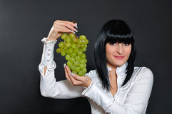 Brunette offers a bunch of grapes Royalty Free Stock Photography