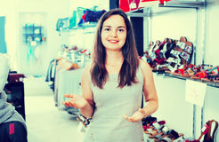 Brunette offers footwear in fashion shoes center Royalty Free Stock Photos