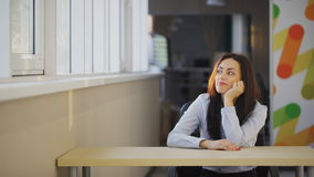 Brunette office worker feels boring on working place indoors. Attractive woman sitting on wooden table, props head with hand, dreaming, looking at large window stock footage
