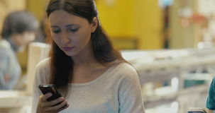 Brunette oman using smartphone in cafe stock video footage
