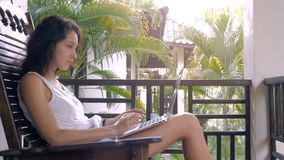 Brunette open and typing on a laptop keyboard in a warm sunny day. Brunette girl opens and typing on a laptop keyboard on a warm sunny day outdoors. on the stock video footage