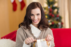 Brunette opening a gift on the couch at christmas Royalty Free Stock Images