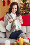 Brunette opening a gift on the couch at christmas Royalty Free Stock Photo