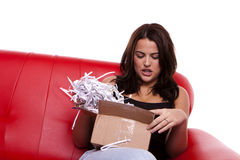 Brunette opening a parcel. Stock Photos