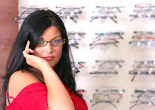 The brunette at the optician. Photo of the charming girl chooses the model of collets to glasses Royalty Free Stock Images