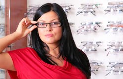 The brunette at the optician. Photo of the charming girl chooses the model of collets to glasses Stock Photography