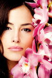 Brunette with orchid. Brunette beauty portrait with pink orchid, studio shot Royalty Free Stock Images