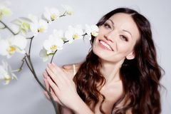 Brunette with orchid flowers Stock Photography