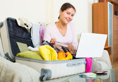 Brunette packing luggage Stock Images