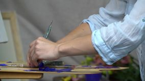 Brunette painter in blouse squeezes blue paint from a tube on the palette, slow motion shooting stock video