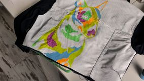 Brunette paints on a denim jacket an illustration of a bull terrier. View from above stock footage