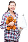Brunette in pajamas holding a pillow and a beloved teddy bear. On a white background Stock Photos