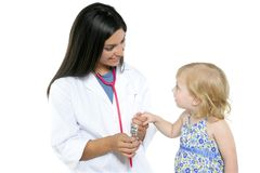Brunette pediatric doctor with blond little girl Royalty Free Stock Image