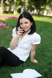 Brunette with a phone. Cute brunette with a phone in the park Royalty Free Stock Photo