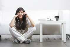 Brunette with phone sitting on floor Royalty Free Stock Image