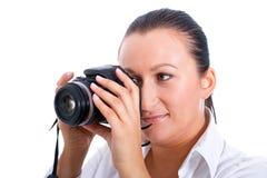 Brunette photographer woman with DSLR. Brunette photographer woman holding camera over white background Stock Photos