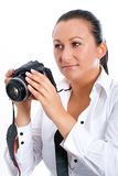 Brunette photographer woman with DSLR camera. Brunette photographer woman holding camera over white background Stock Photo
