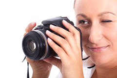 Brunette photographer woman holding camera. Over white background Royalty Free Stock Images