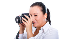 Brunette photographer woman making photos on DSLR. Brunette photographer woman holding camera over white background Stock Photography