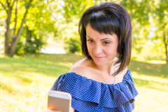 Brunette photographing herself on the phone in the par Royalty Free Stock Photo