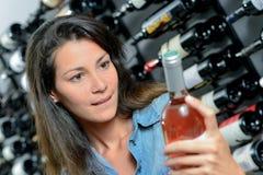 Brunette picking out bottle wine stock photo