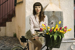 Brunette pin-up on bicycle with color flowers Stock Photography