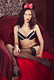 Brunette pin up model posing dressed in underwear and bow of  Mi Royalty Free Stock Photos