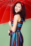 Brunette pin up model posing wearing striped dress Royalty Free Stock Image
