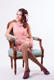 Brunette in a pink dress sitting on a chair in baroque style. Curly-haired brunette in pink dress with soutache technique decorations with flowers sitting on a royalty free stock photos