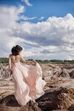 Brunette in pink dress stands on a cliff, the wind ruffles a dre. Ss, a tender image of a girl. Fabulous mountain landscape. Woman in the wind Stock Images