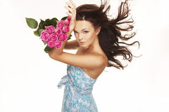 Brunette with pink roses Royalty Free Stock Image