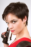 Brunette with pistol. Beautiful dark-haired girl in leather gloves with pistol and pistol holster Royalty Free Stock Photos