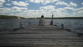 Brunette in plaid sad sitting on an old wooden pier and looks out at the water and forest in the distance.