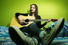Brunette playing guitar on bed Royalty Free Stock Image