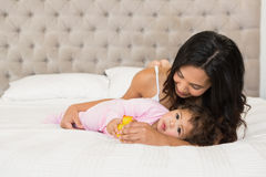 Brunette playing with her baby and a duck. On the bed stock photos