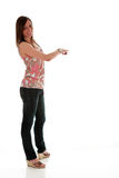 Brunette pointing. Full length girl pointing behind her dressed in pink&white top & jeans white background Royalty Free Stock Photos