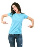 Brunette pointing at her blank light blue shirt Royalty Free Stock Photography