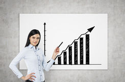 A brunette is pointing out bar chart. A concept of successful business presentation. Concrete wall Stock Images
