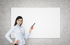 A brunette is pointing out something on the whiteboard. Stock Photo