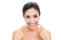 Brunette pointing to mouth and smiling at camera Royalty Free Stock Photography