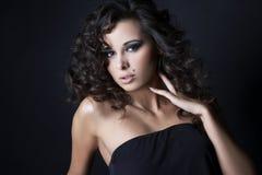 Brunette posing on black background in studio