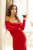 Brunette posing in sexy dress with glass of wine Stock Photos