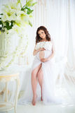 Brunette pregnant girl in interior bath with flowers and tulle curtains Stock Images