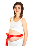 Brunette pregnant woman with red ribbon Stock Image